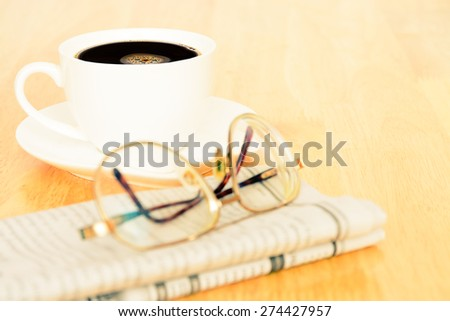 Vintage look of coffee and newspaper on wooden table - stock photo