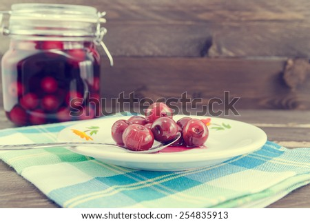 Vintage look of sour cherries on spoon and in the background the jar with sour cherry compote - stock photo