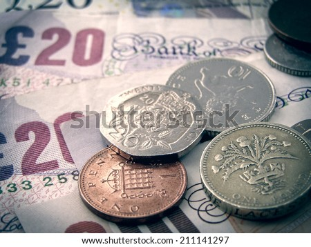 Vintage looking British Pounds banknotes and coins - stock photo
