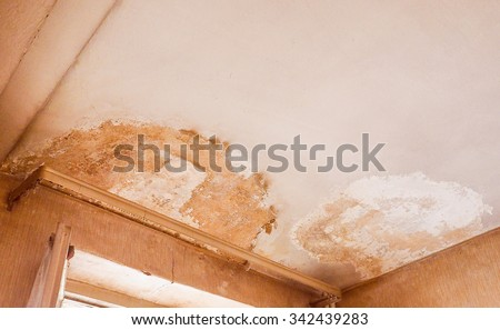Vintage looking Damage caused by damp and moisture on a ceiling - stock photo