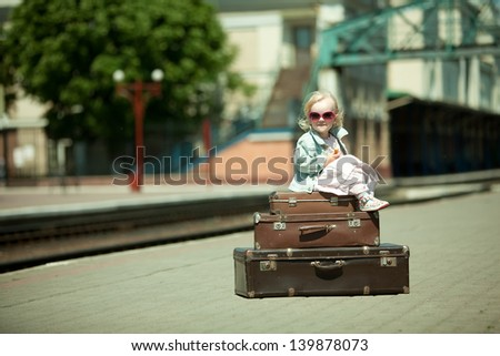 Vintage looking picture of small girl with luggage at the railway station - stock photo