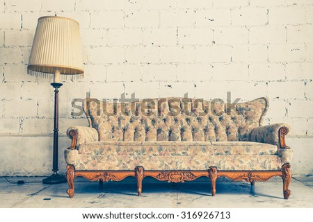 Vintage luxury yellow sofa with white brick wall background  - stock photo