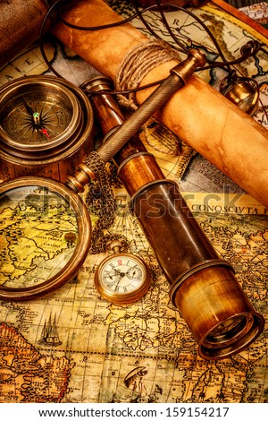 Vintage magnifying glass, compass, telescope and a pocket watch lying on an old map. - stock photo