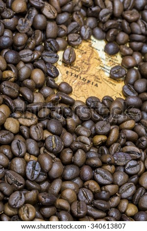 Vintage map of Ethiopia covered by a background of roasted coffee beans. This nation is between the five main producers and exporters of coffee. Vertical image. - stock photo