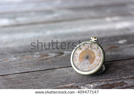 Vintage mechanical clock without hands on the wooden flooring. The old pocket watch. - stock photo
