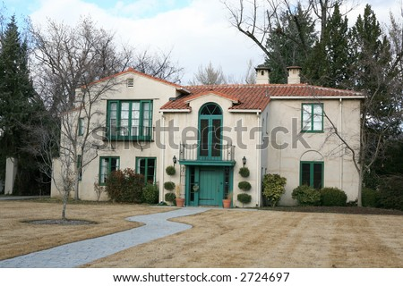 Vintage Mediterranean style house with golden grass and clouds - stock photo