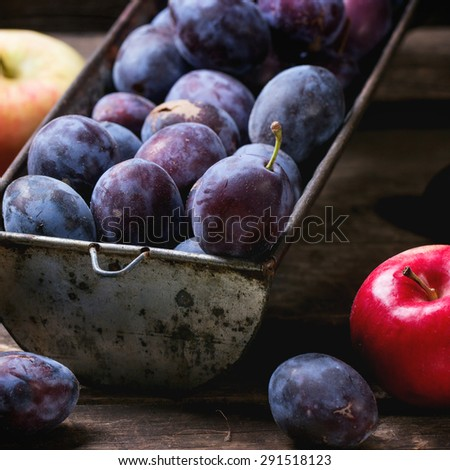 Vintage metal bowl with plums and apples over old wooden table. Square image with selective focus - stock photo