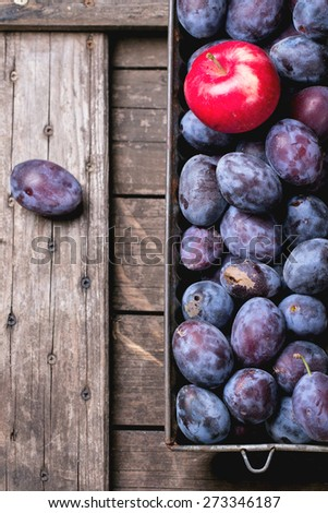 Vintage metal bowl with plums and apples over old wooden table. Top view. See sries - stock photo