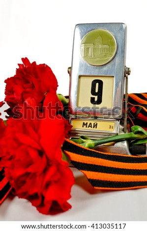 Vintage metal desk calendar with 9 May date and George ribbon with red carnations bouquet -  Victory Day concept isolated on white background. Selective focus at the calendar.  - stock photo