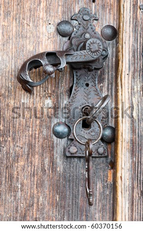 Vintage metal handle and key at wooden door - stock photo