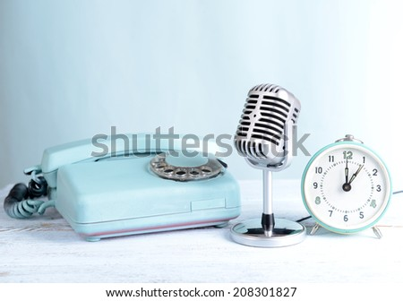 Vintage microphone,phone and alarm clock on table on light blue background - stock photo