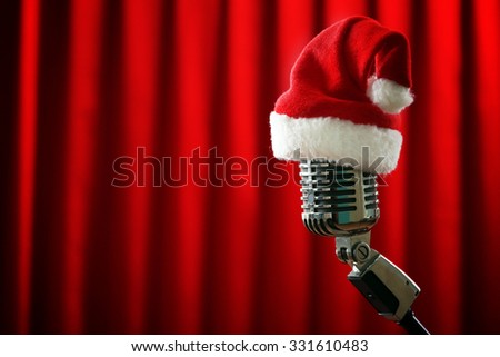 Vintage microphone with Christmas hat on red curtain background - stock photo