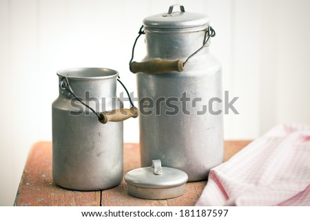 vintage milk cans on old wooden table - stock photo