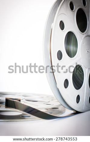 Vintage 35 mm movie cinema reel on white background film unrolled and copy space vertical frame - stock photo
