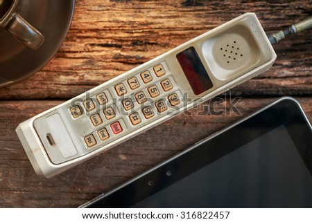 vintage mobile phone with tablet on old table (vintage style) - stock photo
