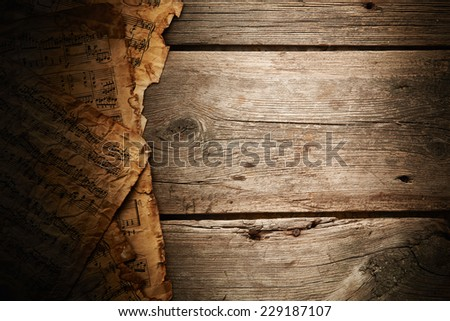 Vintage music sheets on wooden background - stock photo
