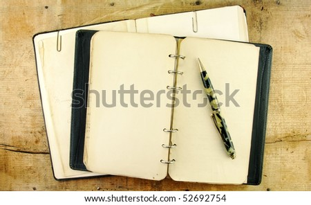 Vintage notebook and mechanical pencil on a rustic wooden table. - stock photo