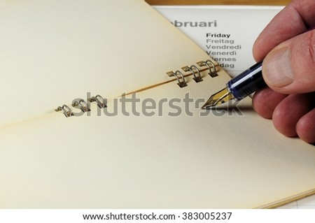 Vintage notebook with calendar and male hand writing with fountain pen. - stock photo