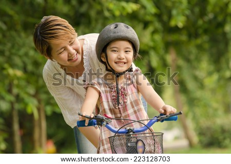 Vintage of little Asian child with mother practice to riding a bicycle - stock photo