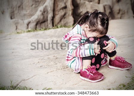 Vintage of little child girl crying and sad about an empty brick wall - stock photo