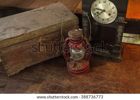 Vintage oil lamp ,old wooden box and alarm clock on old wooden touch-up in still life concept ,dark tone - stock photo