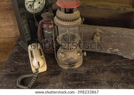 Vintage oil lamp ,old wooden box and alarm clock on old wooden touch-up in still life concept,dark tone - stock photo
