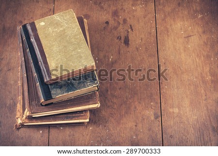 Vintage old books on grunge wooden table background. Retro instagram style filtered photo - stock photo