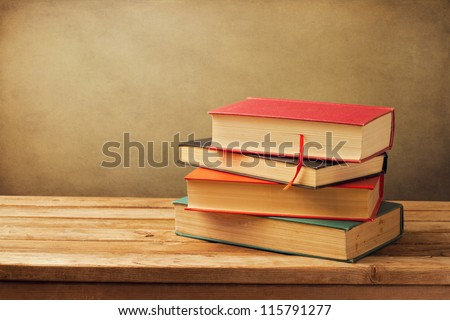 Vintage old books on wooden deck tabletop against grunge wall - stock photo