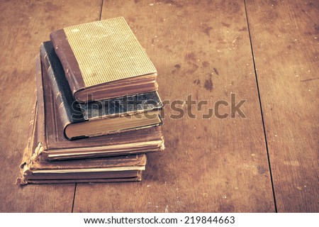 Vintage old books on wooden desk. Retro style filtered photo - stock photo