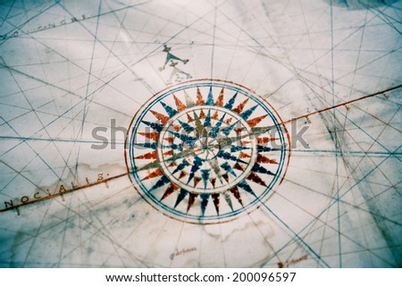 Vintage old compass on vintage map. Shallow depth of field with focus on the compass. - stock photo