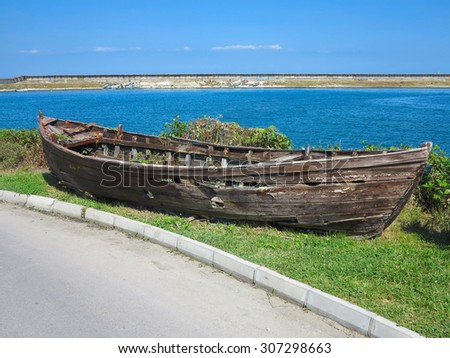 Vintage old damaged boat near sea coast - stock photo