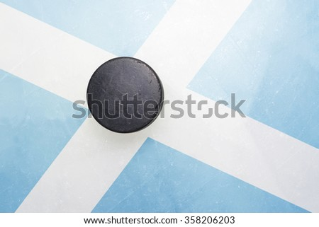 vintage old hockey puck is on the ice with scotland flag - stock photo