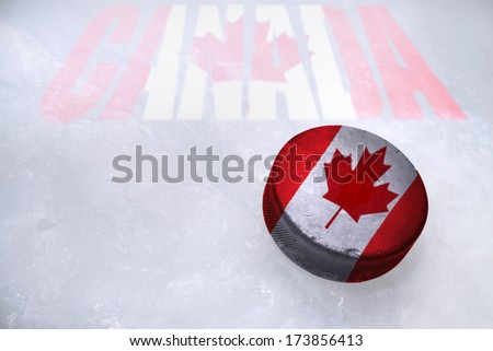 Vintage old hockey puck with the Canada flag is on the ice - stock photo