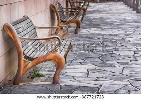 vintage old rusty bench beside red brick wall. - stock photo