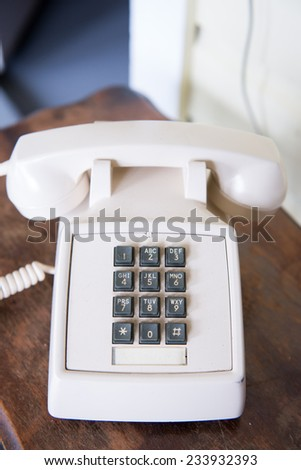Vintage old telephone, on rustic wooden table - stock photo