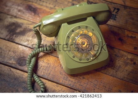 Vintage old telephone on wooden table background - stock photo