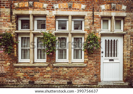Vintage old wall with door and windows. Typical architecture of Bruges, Belgium. Image used vintage tone filter. - stock photo