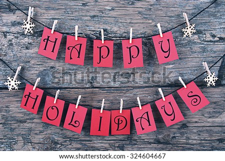 Vintage Or Shabby Chic Wooden Rustic Background. Red Tags With Happy Holidays Hanging On A Line. Snowflakes Hanging On Cloth Pegs. Christmas Card For Seasons Greetings - stock photo