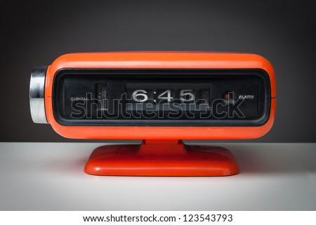 Vintage orange alarm clock on a dark background - stock photo
