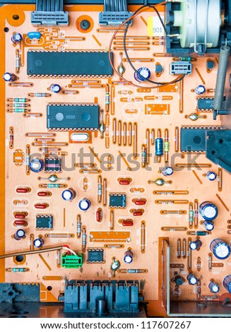 Vintage orange populated printed circuit board PCB showing the conductive traces vias the through-hole paths to the other surface and some mounted electrical components - stock photo