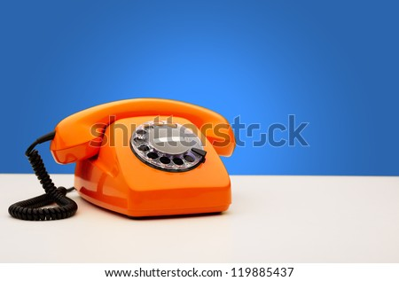 Vintage Orange Telephone On Blue Background - stock photo
