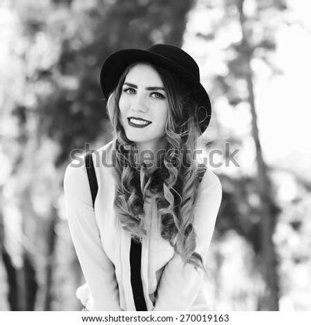 Vintage outdoor lifestyle portrait of pretty funny hipster woman. Modern urban girl having fun. Beautiful young girl in a hat. Black and white portrait, square format with a retro instagram filters. - stock photo