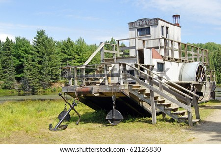 Vintage paddle wheel boat used for moving rafts of logs - stock photo