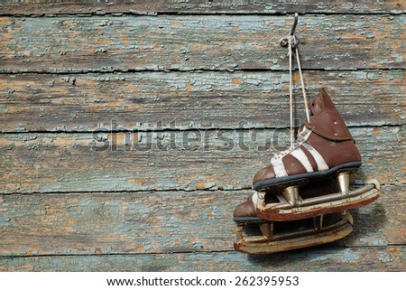 vintage pair of mens  ice skates hanging on a cracked paint wall - stock photo