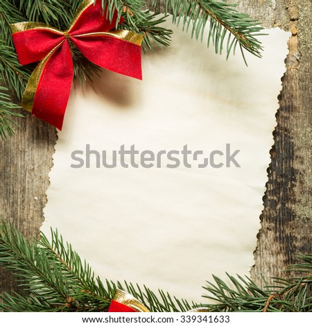 Vintage paper card with christmas decoration. Christmas tree branches with red bows and copy space on wooden background - stock photo