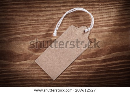 vintage paper price tag label on old wooden boards close up - stock photo