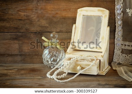 vintage pearls , antique wooden jewelry box with mirror and perfume bottle on wooden table. filtered image  - stock photo