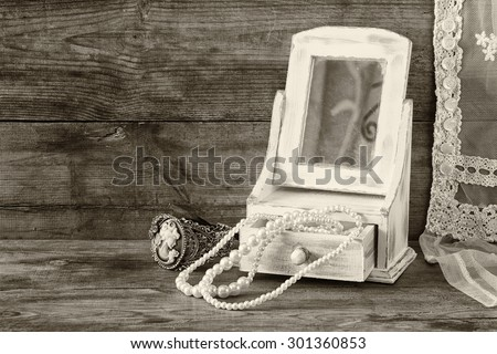 vintage pearls , antique wooden jewelry box with mirror and perfume bottle on wooden table. black and white style photo  - stock photo