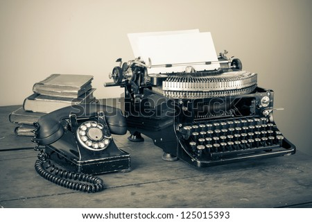 Vintage phone, old typewriter, books on table desaturated photo - stock photo