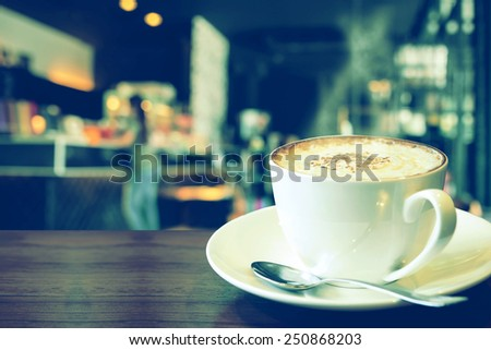 Vintage photo, a cup of cappuccino with coffee shop background - stock photo